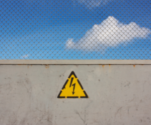 Caution Sign On Brick Wall With Sky Above To Invite Companies To Publish A Toll Free Number On Their Website.